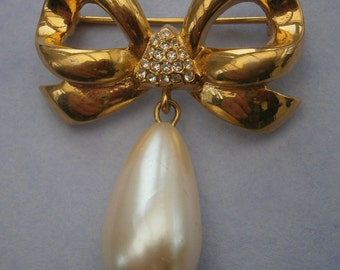 B966) A lovely gold tone metal vintage marked WD diamante drop faux pearl bow brooch