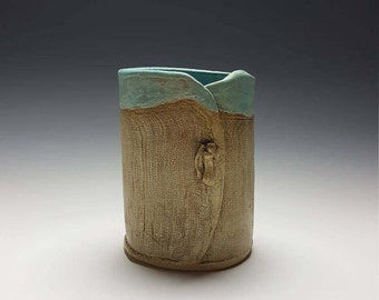 Handmade ceramic vase by Potteryi. Rustic utensil holder with turquoise interior and textured exterior.