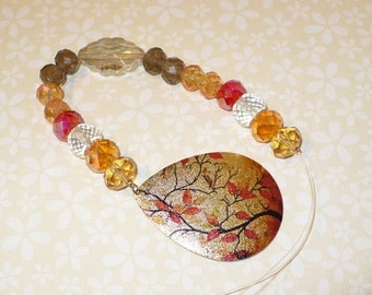 Crystal suncatcher in warm yellow and orange hues with adorned by a metal pendant with red, orange and yellow leaves.