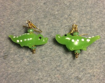 Opaque lime green lampwork alligator bead earrings adorned with lime green Chinese crystal beads.