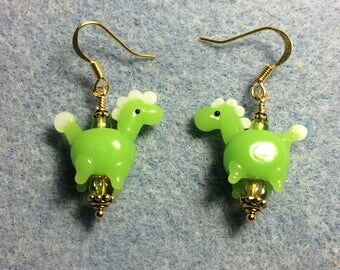 Opaque olive green lampwork horse bead earrings adorned with olive green Czech glass beads.