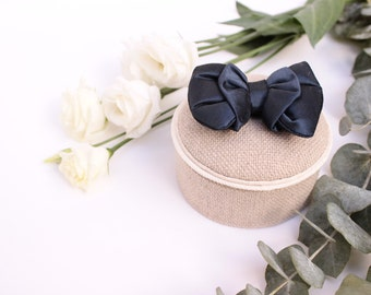 Beige ring bearer box with an oversized navy blue silk bow.
