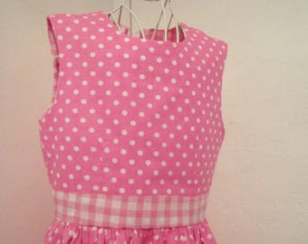 Classic summer dress in bright pink polka dot cotton with gingham belt and trim. age 8