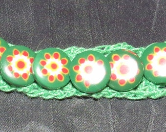 Green crochet bracelet with green/red accent buttons