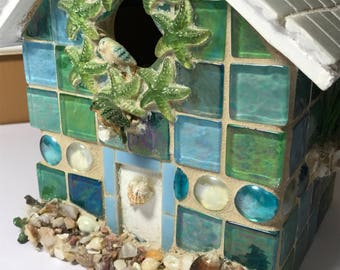Mosaic and tile birdhouse decorated in a beach scene