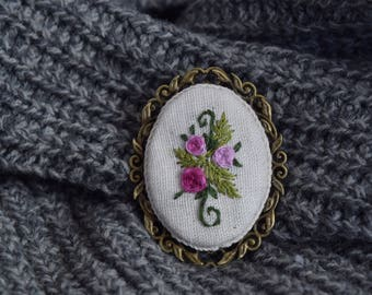 Brooch with embroidered roses.