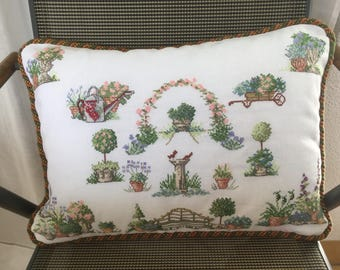 Embroidered cushion with garden motif