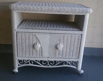 Wicker TV cart with wrought iron designs.