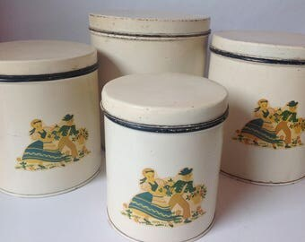 Set of 4 Vintage Tin Canister Set White Background With Blue and Yellow Pennsylvania Dutch Pattern Boy and Girl