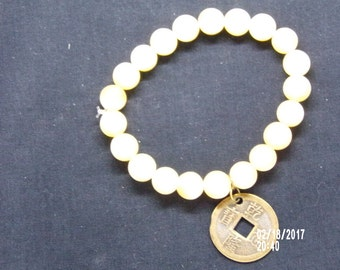 B021716 Medium Size Cream Colored Ceramic Beaded Bracelet with Chinese Good Luck Charm.