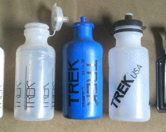 vintage Trek bicycle waterbottles + cage. 1970's thru the early 1990's. Lot of 4 bottles and 1 cage
