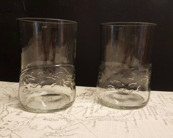 A pair of drinking glasses made from unusual beer bottles.