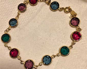 Vintage Swarovski Crystal Bracelet with Swan Symbol. It has Green, Red, Purple, and Blue Flat Back Crystals Set in Goldtone Settings. (D13)