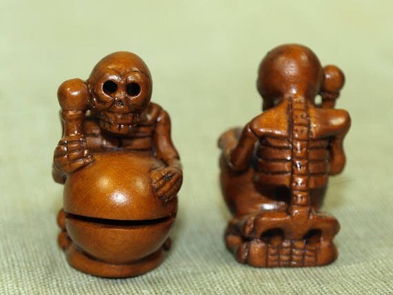 Hand carved boxwood ojime bead skeleton playing on