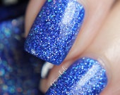 "Nail polish - ""Bonus Round"" silver holographic glitter in a royal blue jelly base"