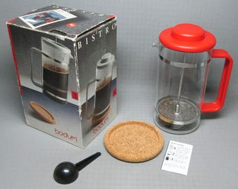 Bodum Bistro red coffee press , box says 8 cups , comes with cork coaster , scoop , booklet french press