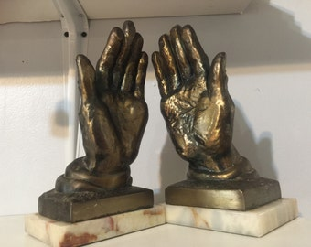 Metal and marble hands. Bookends. Interior design.