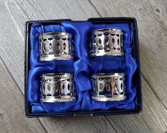 Four silver plated napkin rings, in their original box