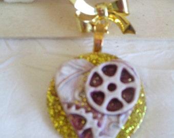 Broche métal doré porcelaine froide sur estampe en bois doré