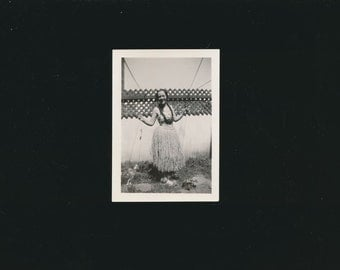 vintage photo of a young lady in a grass hula skirt, 1940's.