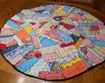 Round Table Topper Patches appliqued on green print fabric.
