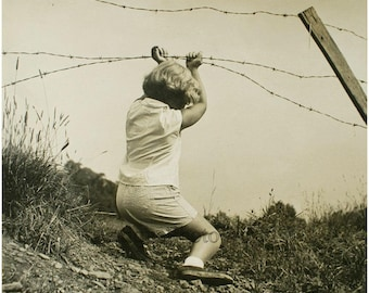 Child holding barbed wire vintage photo by E. Lettau