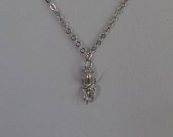 A quirky and tiny matte rhodium plated ant charm pendant necklace on a fine sterling silver chain