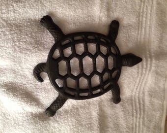"Antique medal trivet made in the shape of a turtle.  It has 4 legs to hold it up off the table and the size is 7""L X 6""""W. Shape is oblong."