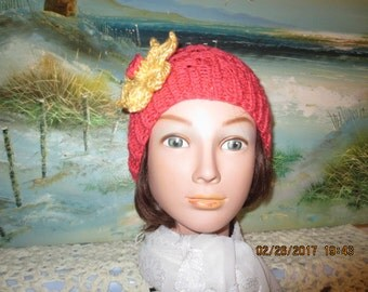 Unique knitted coral color ladies spring hat with yellow flower pin.