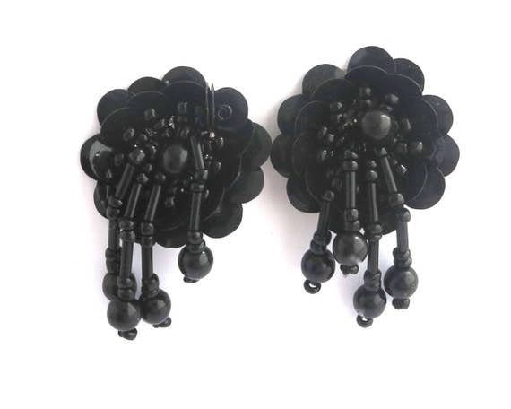 Black sequinned and beaded earrings in shape of flower with dangles of beads, silver metal clip ons, handmade, circa 1960s