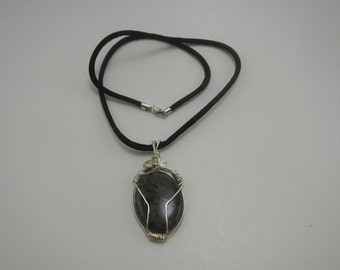 Green cabochon stone wrapped with sterling silver wire