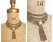Dramatic multi strand gold chain necklace with latge tassel.