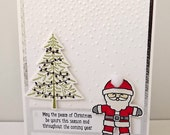 Christmas card, with Santa Claus and a Christmas tree with snow embossed background