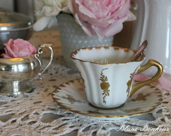 Porcelaine de France: White tea cup and saucer with gold hand painted flowers