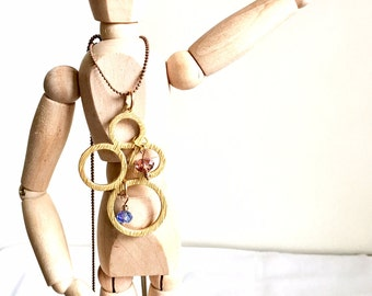 Handmade necklace with gold pendant and crystal blue and mauve.  Brown chain-