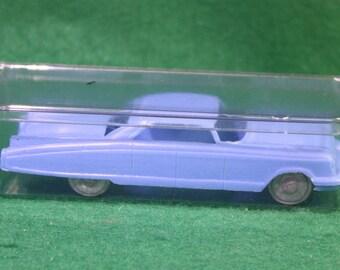 Vintage sparse blue plastic 1960 Cadillac sedan with metal wheel and axles