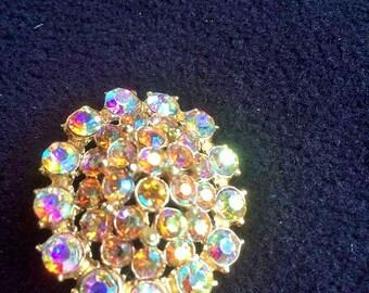 Aurora Borealis rhinestone encrusted graduated oval gold tone brooch