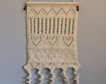 Wall art hanging, decor, hand knitted in cream aran wool, lacy patterns and heart motifs, spiral tassels and wooden beads with red patterns
