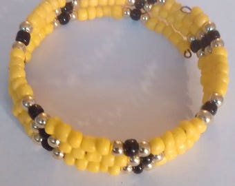 bracelet made with yellow black and gold seed beads and memory wire