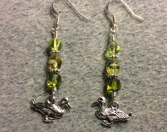 Silver duck charm dangle earrings adorned with light green Czech glass beads.