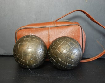 2 vintage French Boules Lyonnaises with leatherette satchel carrying case . Boules are in heavy bronze. Playing quality.
