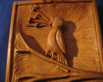 Vintage carved singing bird has his hand on pine wood