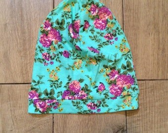 Girl's slouchy beanie in aqua green and pink floral fabric.