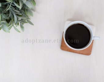 Styled Stock Layflat Photo White with Coffee, Wooden Coaster, and Green Plant
