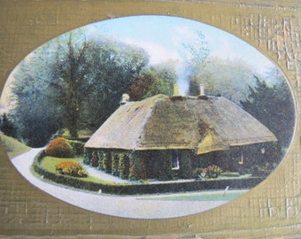 A Killarney Homestead postcard (unposted) / Gold embossed postcard / thatched roof cottage / Printed in Saxony /