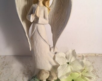 A sparkly Woman  Angel figurine Praying with a Daisy  in her hair - standing in A Garden  of Mushrooms