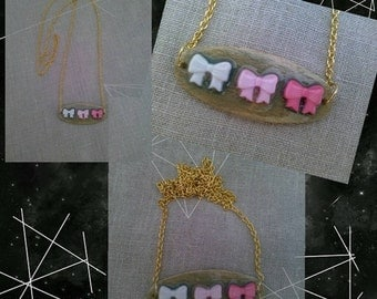 light Pink, dark pink, and white bow necklace with gold toned chain