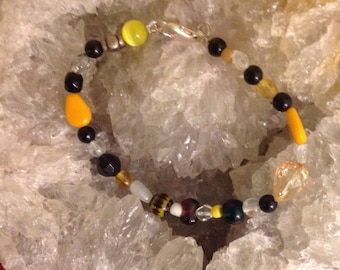 Handmade Beaded Bracelet with Ecclectic beads of various materials with yellow/orange colors.