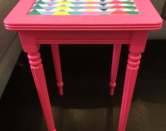 Funky little side table painted in bright neon pink with decoupage graphic print insert