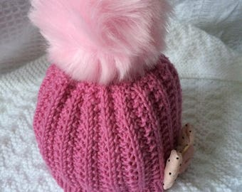 Hand knitted baby hat with over sized faux fur pom pom